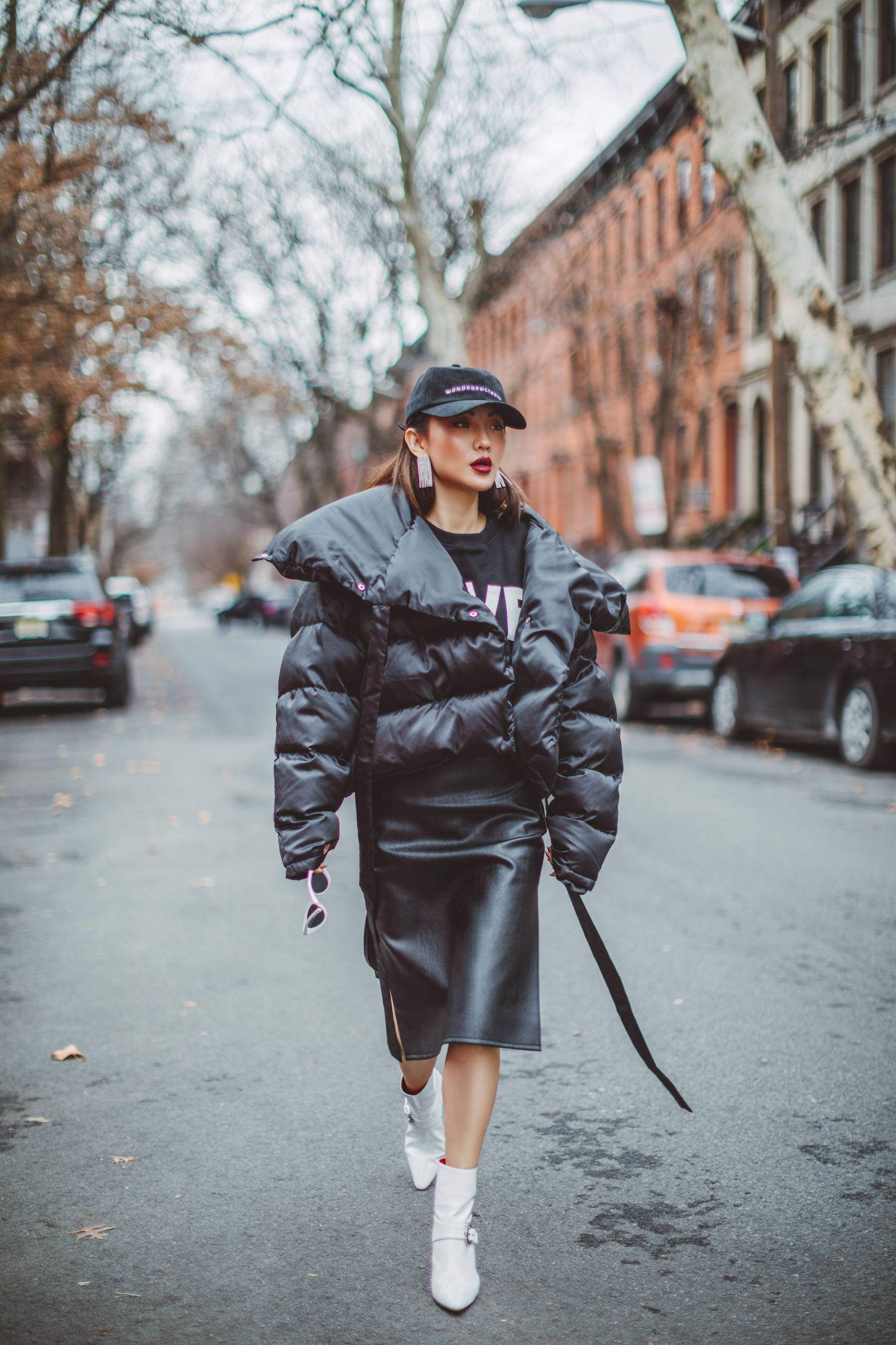 How to Look Stylish in a Quilted Puffer Jacket // Notjessfashion.com // Black quilted puffer jacket, white ankle boots, black oversized sweater, leather skirt, urban outfit, edgy fashion look, baseball cap, pink sunglasses, new york fashion blogger, asian blogger, how to dress edgy, new york street style, edgy street style