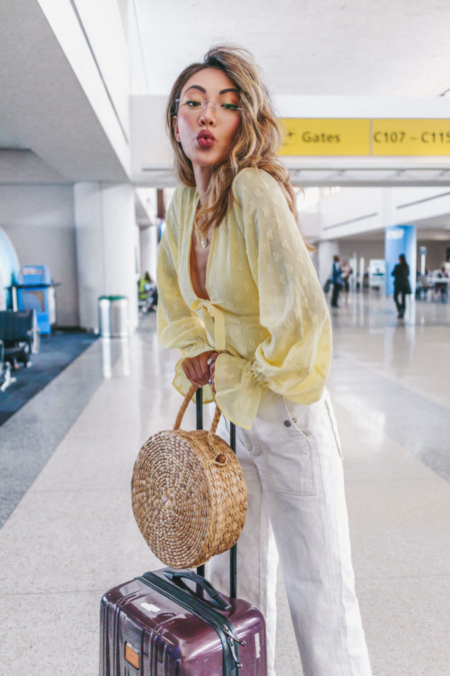 jessica wang wearing a yellow keyhole blouse with white jeans at the airport while sharing her travel essential items // Jessica Wang - Notjessfashion.com