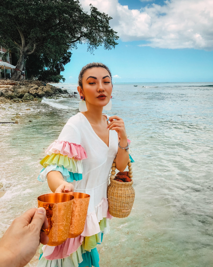 jessica wang drinking a cocktail in barbados and sharing her tropical vacation packing list