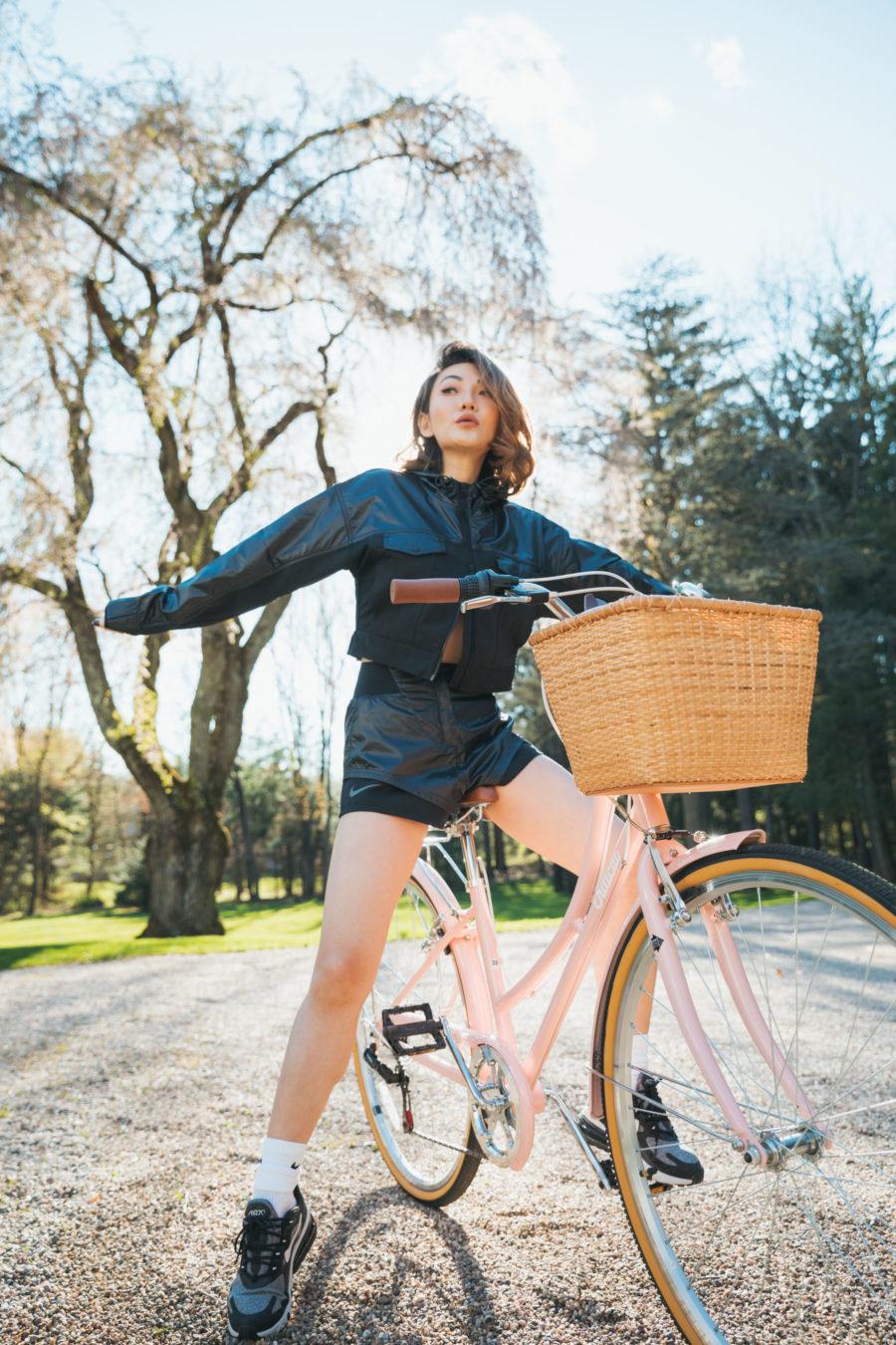 jessica wang wearing a black track jacket, black nike shorts, and nike shoes on a bike while sharing her self-care tips // Jessica Wang - Notjessfashion.com