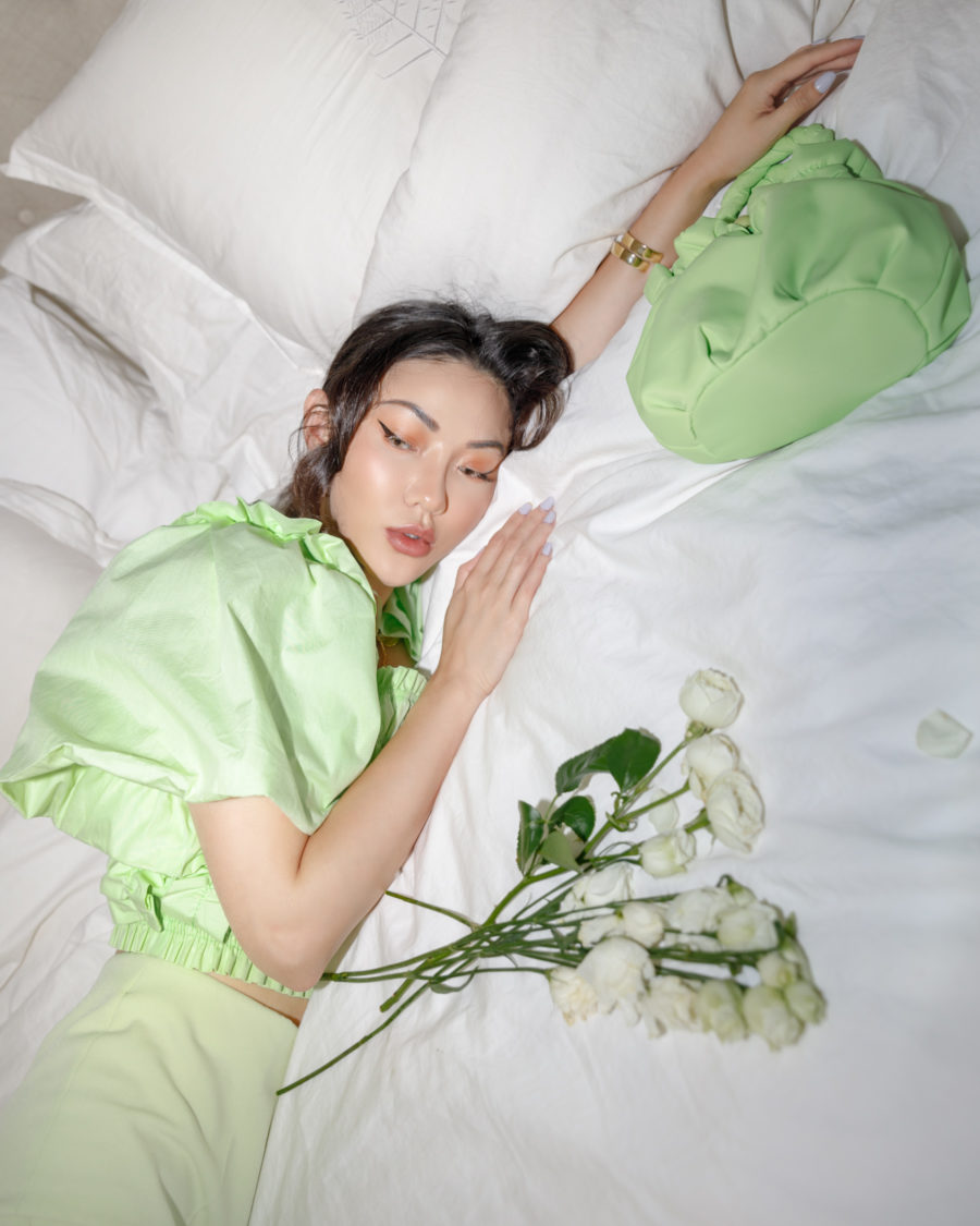 jessica wang wearing green outfit on bed with roses sharing nordstrom anniversary sale home finds // Jessica Wang - Notjessfashion.com