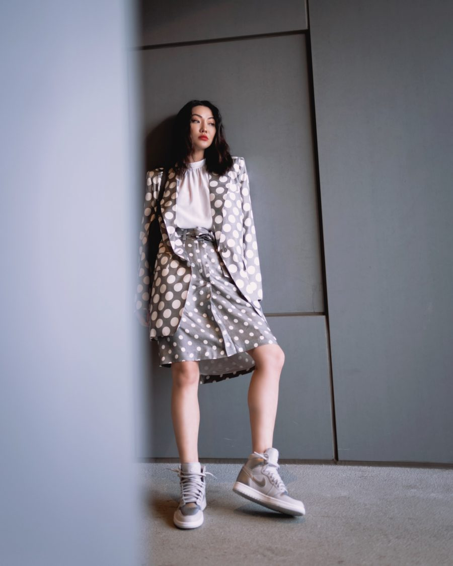 jessica wang wearing a polka dot blazer and polka dot midi skirt with gray sneakers while sharing casual spring suits for women // Jessica Wang - Notjessfashion.com